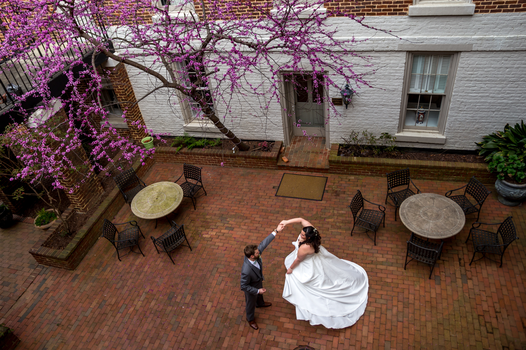 newlyweds - husband spinning his bride in a brick courtyard © MKM Photography